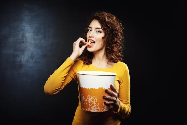Mulher atraente, comendo pipoca de queijo, olhando satisfeito e feliz Foto gratuita