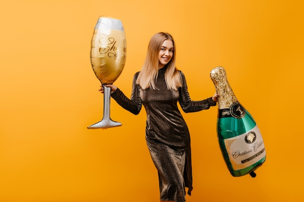 Mulher atraente dançando na laranja com garrafa de champanhe. retrato interior de jocund mulher caucasiana comemorando aniversário com vinho. Foto gratuita