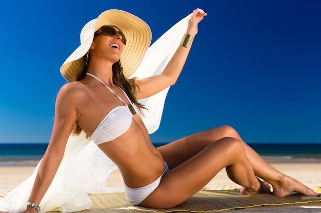 Mulher atraente de biquíni sorri para o sol na praia Foto Premium