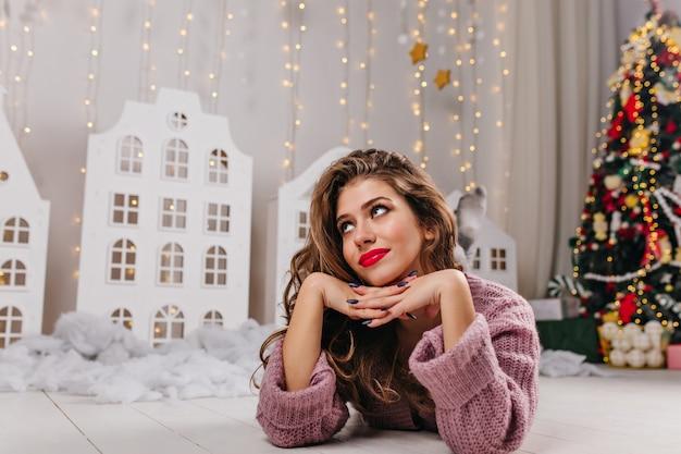 Mulher atraente de cabelos castanhos com lábios vermelhos e sorriso doce encontra-se no quarto branco decorado, cheio de brinquedos de natal e uma árvore de natal exuberante. Foto gratuita