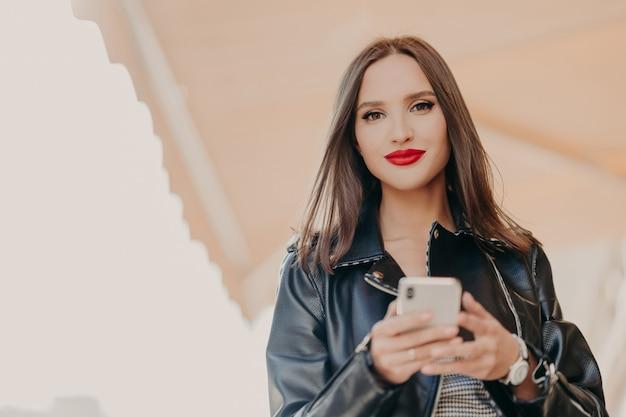 Mulher atraente de cabelos escura com lábios pintados de vermelhos, vestida de jaqueta de couro preta, segura o celular moderno Foto Premium