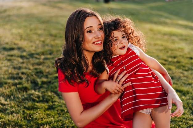Mulher atraente de cabelos escuros sentado na grama com a filha. foto ao ar livre de uma garota cacheada rindo e abraçando a irmãzinha na natureza Foto gratuita