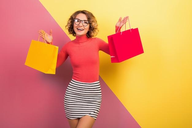 Mulher atraente e animada sorridente em roupa colorida elegante segurando sacolas de compras Foto gratuita