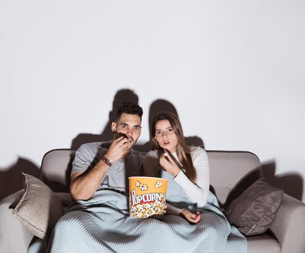 Mulher atraente e bonito homem assistindo tv e comendo pipoca no sofá Foto gratuita