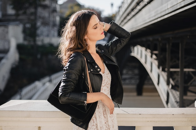 Mulher atraente e elegante andando na rua com roupa da moda, bolsa de camurça, jaqueta de couro preta e vestido de renda branca estilo primavera outono Foto gratuita