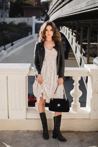 Mulher atraente e elegante posando na rua com roupa da moda, bolsa de camurça, vestindo jaqueta de couro preta e vestido de renda branca, botas de cano alto, estilo primavera outono Foto gratuita