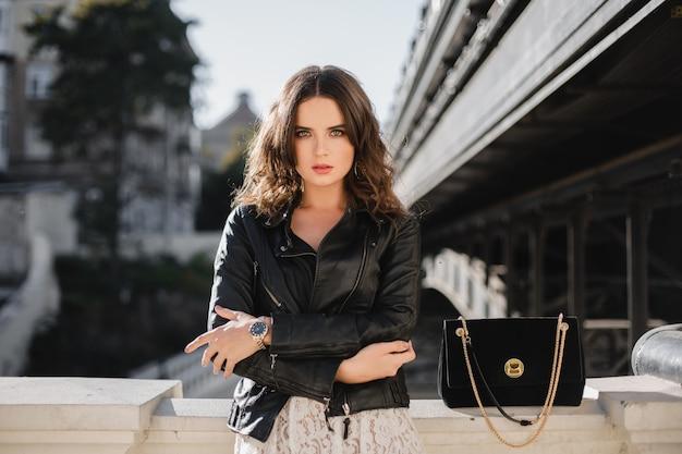 Mulher atraente e elegante posando na rua com roupa da moda, bolsa de camurça, vestindo jaqueta de couro preta e vestido de renda branca, estilo primavera outono Foto gratuita
