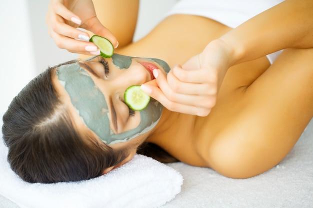 Mulher atraente e engraçada com máscara no rosto no spa Foto Premium