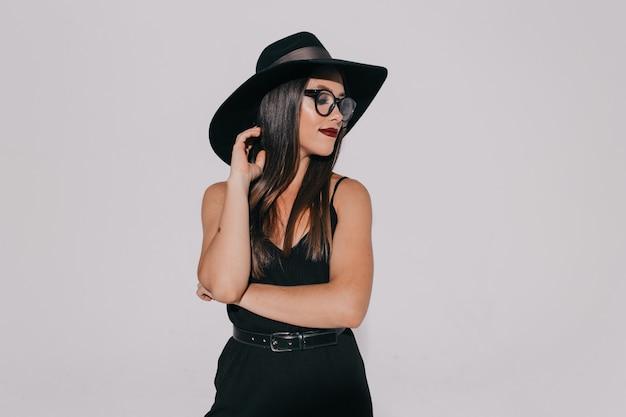 Mulher atraente elegante em roupa preta com óculos com batom de videira posando sobre parede cinza. Foto gratuita