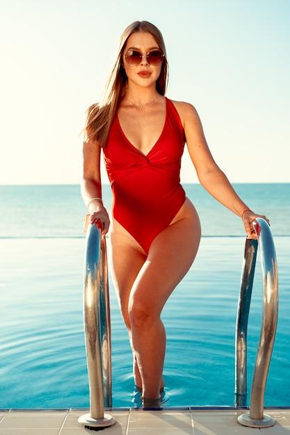 Mulher atraente em traje de banho vermelho e óculos de sol saindo da piscina Foto Premium