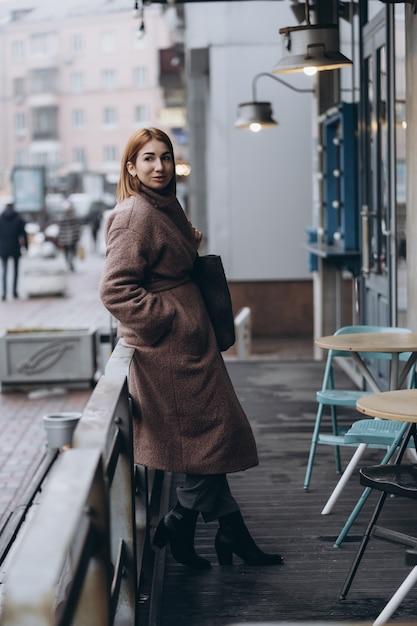 Mulher atraente em trench coat na rua da cidade Foto gratuita