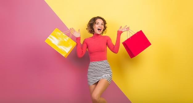 Mulher atraente em uma roupa elegante e colorida segurando sacolas de compras com expressão de surpresa Foto gratuita