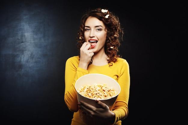Mulher atraente engraçada comendo pipoca doce salgada saborosa no cinema Foto gratuita