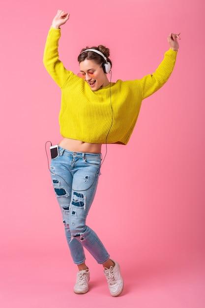 Mulher atraente feliz e engraçada dançando ouvindo música em fones de ouvido, vestida com roupa de estilo colorido moderno, isolada no fundo rosa do estúdio Foto gratuita