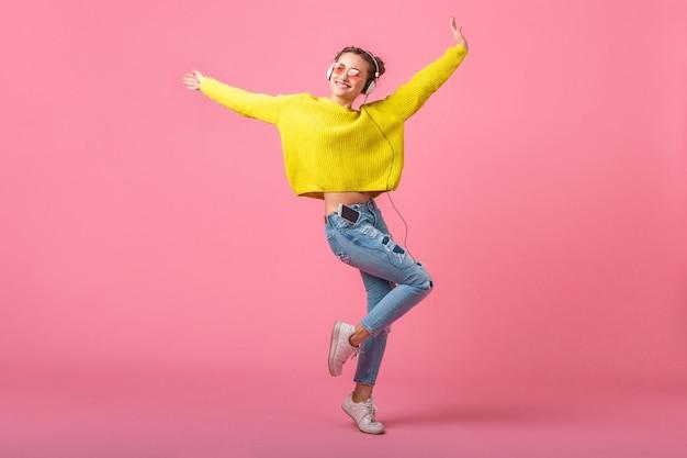 Mulher atraente feliz e engraçada pulando ouvindo música em fones de ouvido, vestida com roupa de estilo colorido moderno, isolada na parede rosa, vestindo suéter amarelo e óculos escuros, se divertindo Foto gratuita