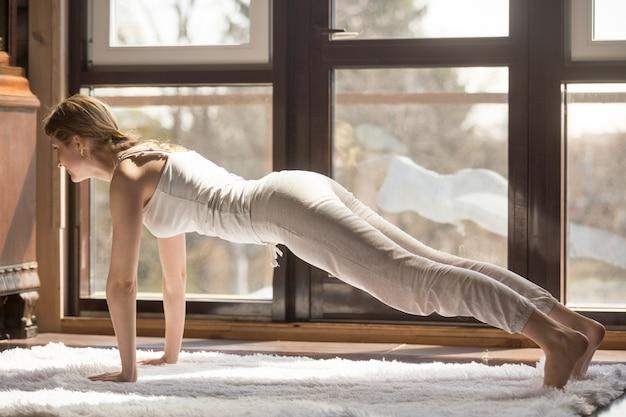 Mulher atraente jovem iogue em pose de prancha, interior de casa Foto gratuita