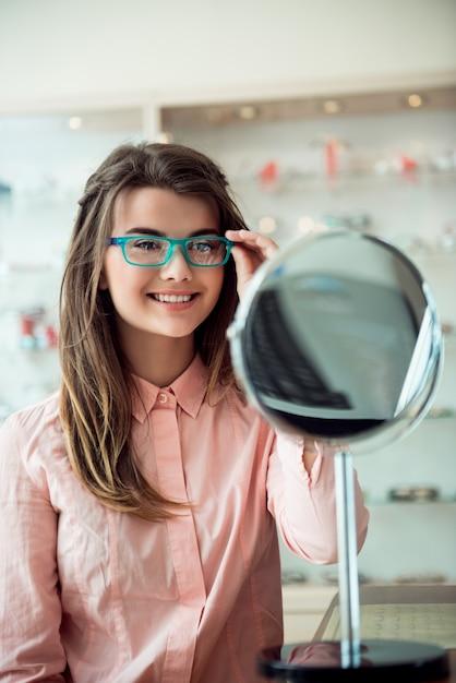 Mulher atraente na consulta no consultório oftalmológico Foto gratuita