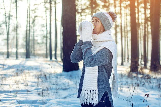 Mulher atraente no inverno, bebendo chá quente na luz solar Foto Premium