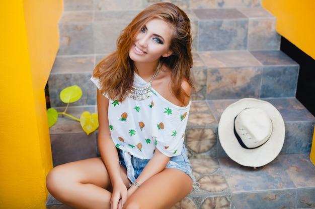 Mulher atraente no verão, sorrindo, usando um chapéu de palha, sentada descalça em uma camiseta impressa, férias da moda Foto gratuita