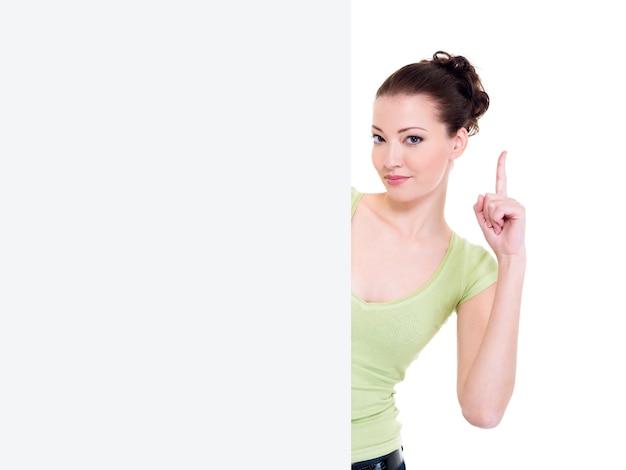 Mulher atraente olhar para fora do banner em branco com levantar o dedo indicador. conceito de ideia Foto gratuita