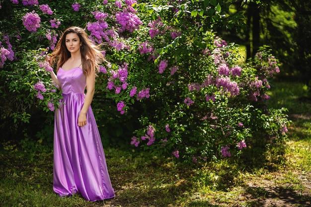 Mulher atraente perto de uma árvore lilás florescendo. seus cabelos tremulam ao vento Foto Premium