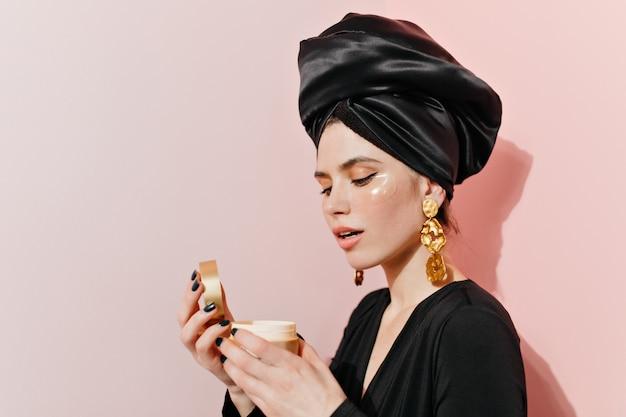 Mulher atraente posando com creme facial e tapa-olhos Foto gratuita