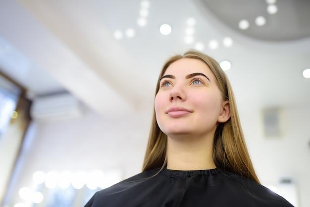 Mulher atraente, recebendo cuidados faciais no salão de beleza. sobrancelhas perfeitas de arquitetura. cuidados faciais e maquiagem. Foto Premium
