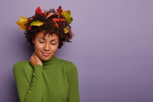 Mulher atraente relaxada com penteado afro, toca o pescoço, fica com os olhos fechados, tem olhar repousante, usa folhas no cabelo, roupas verdes Foto gratuita