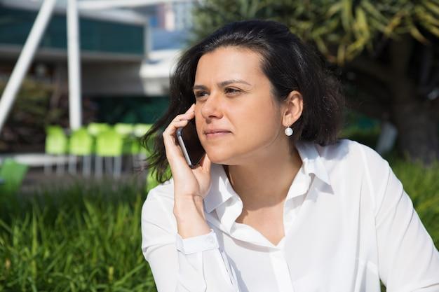 Mulher atraente séria falando no celular ao ar livre Foto gratuita