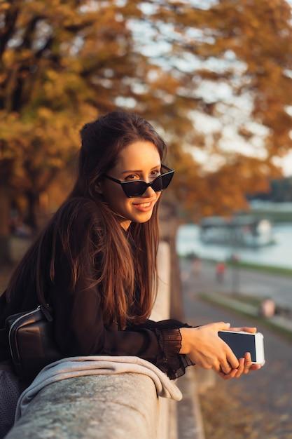 Mulher atraente usando smartphone ao ar livre no parque Foto gratuita