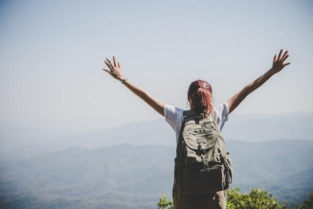 Mulher atrativa caminhante braços abertos no pico da montanha, aproveite com a natureza. conceito de viagem. Foto gratuita