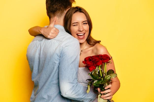 Mulher atrativa com rosas vermelhas que pisc e que mostra um polegar ao abraçar seu noivo. Foto gratuita