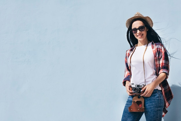 Mulher atrativa de sorriso que mantém a câmera que está contra a parede azul Foto gratuita
