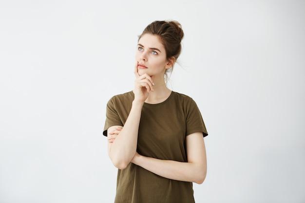 Mulher atrativa nova que pensa com mão no queixo que olha à distância. Foto gratuita