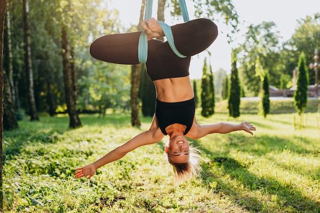 Mulher atrativa que pratica a ioga da mosca na cabeça da árvore para baixo. conceito yoga Foto Premium