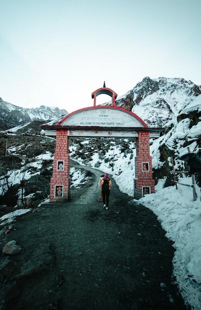 Mulher atravessando um portão de tijolos em terreno montanhoso Foto gratuita
