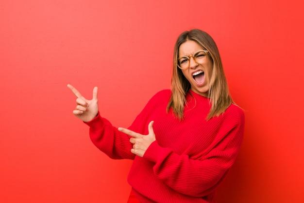 Mulher autêntica jovem carismática pessoas reais contra uma parede apontando com o dedo indicador para um espaço de cópia, expressando emoção e desejo. Foto Premium