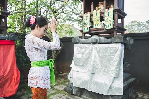Mulher balinesa fazendo ritual oferecendo sang canang e orando Foto Premium