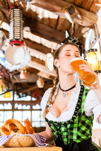 Mulher bávara bebendo cerveja de trigo Foto Premium