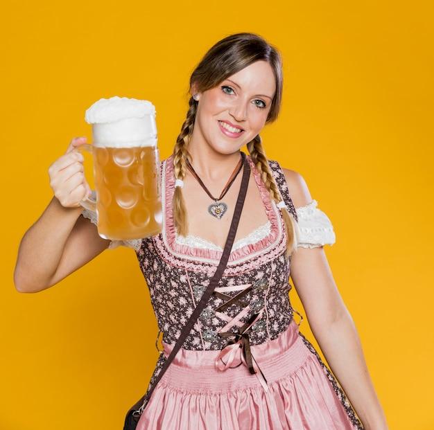 Mulher bávara positiva que guarda a caneca de cerveja Foto gratuita