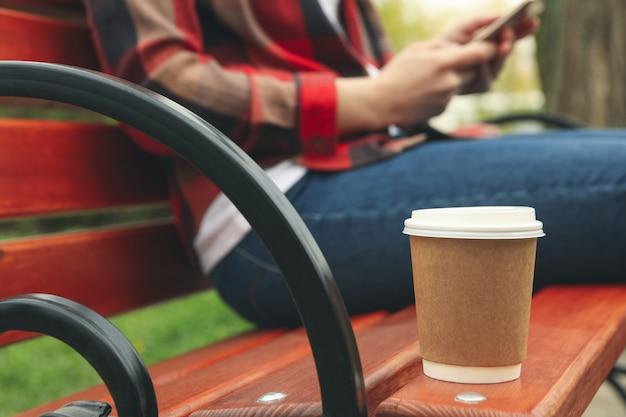 Mulher bebe café e usa smartphone no parque. pausa para o almoço Foto Premium