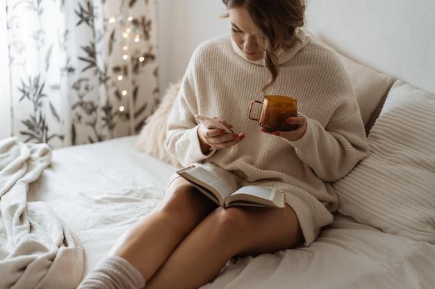 Mulher bebendo chá quente e usando o telefone. estilo de vida confortável. Foto Premium