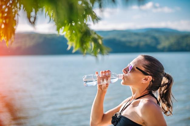 Mulher beber água de garrafa de pet Foto Premium