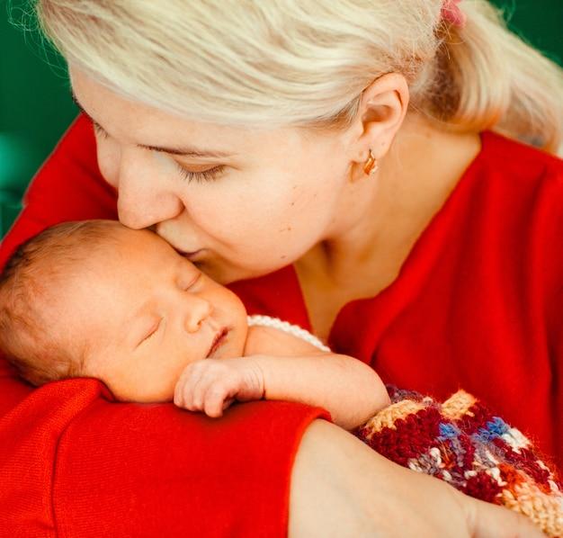 Mulher beija terno recém nascido em seus braços Foto gratuita