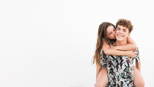 Mulher, beijando, dela, namorado, levando, passeio, costas, contra, branca, fundo Foto gratuita