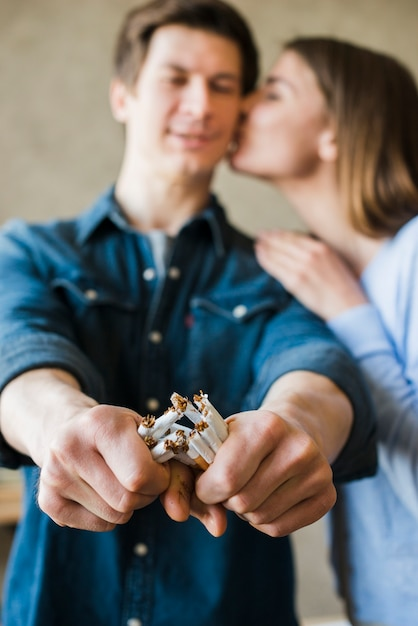 Mulher, beijando, dela, namorado, quebrada, pacote cigarros Foto gratuita