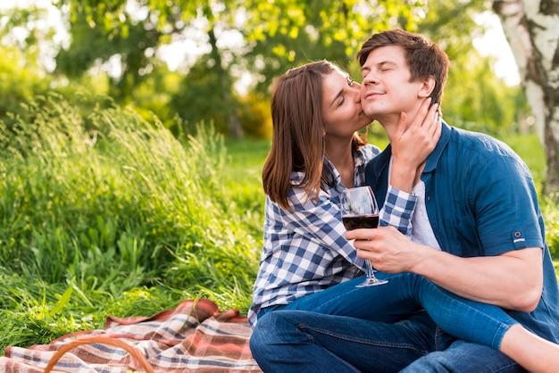 Mulher, beijando, homem, bochecha, enquanto, tendo piquenique Foto gratuita