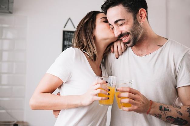 Mulher, beijando, homem, enquanto desfruta de suco Foto gratuita
