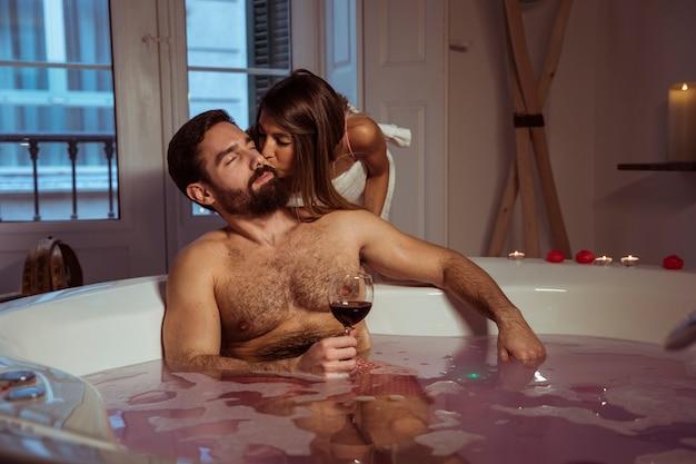 Mulher, beijando, homem jovem, com, vidro, de, bebida, em, banheira spa Foto gratuita