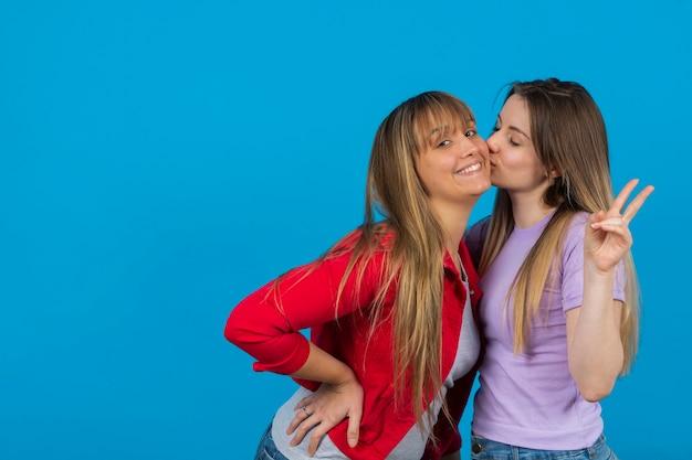 Mulher beijando sua namorada de infância Foto gratuita